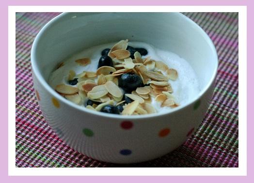 Geschlagene Kokosmilch mit Blaubeeren und Mandelblättchen.